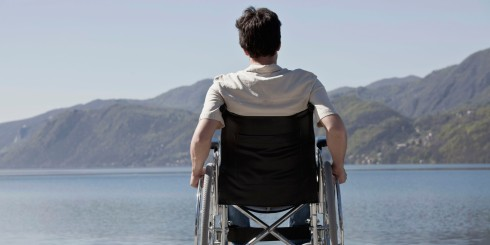 Caucasian man in wheelchair sitting on dock
